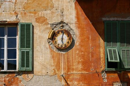 dilapidated: Symbolism, temporary changes: vintage watch on dilapidated building in the Sospel village medieval French Stock Photo