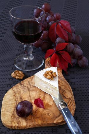 morsel: Autumn still life: grapes, scarlet leaves, a morsel of French cheese Coulommiers and glass of red wine