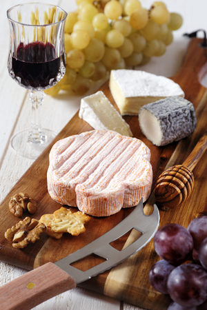 collation: Cheese plate: French soft cheeses, red and green grapes, walnuts, crackers and a glass of red wine Stock Photo