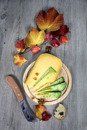 cheese platter: Cheese platter: solid cheese and autumn leaves on dark background Stock Photo