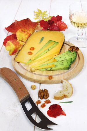collation: Cheese platter: solid cheese, autumn leaves and glass of white wine