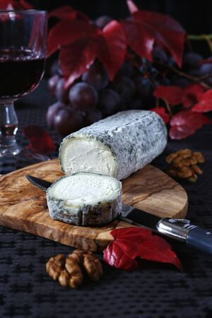 collation: Autumn still life: grapes, scarlet leaves, French blue cheese and glass of red wine