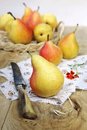 sweet and savoury: Yellow pears in wicker basket on wooden background