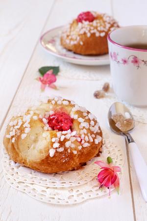 flores fucsia: té de cinco en punto en rosa: dos bollos franceses, flores fucsias y taza de té