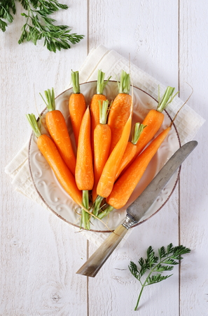 Fresh peeled carrots on green tops, vintage knife on white wood background Archivio Fotografico