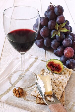 cow's milk cheese: French soft cows milk cheese Brie, fruit and glass of red wine