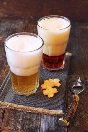bottle opener: Two glasses of beer, light and dark, crackers and beer bottle opener Stock Photo