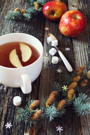 taza de te: el estado de �nimo de A�o Nuevo: taza grande de t� negro, dos manzanas rojas y ramas de pino. imagen virada