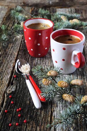Christmas mood: twee kopjes koffie en dennentakken op oude houten oppervlak