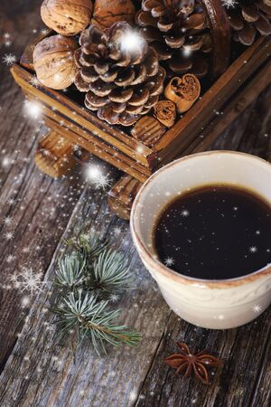 christmas spirit: Christmas spirit: cup of coffee, pine cones in basket and flying snowflakes