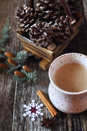 christmas spirit: Christmas spirit:  mug of cappuccino and pine cones in basket Stock Photo