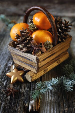 basket: Christmas basket with tangerines, cinnamon sticks and pine cones
