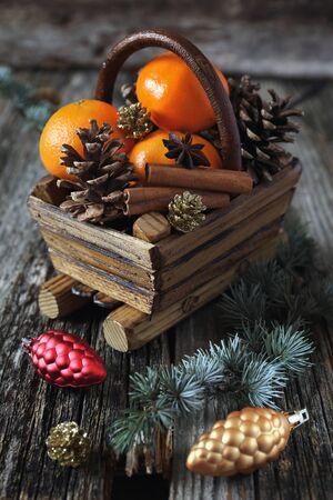 festive pine cones: Christmas basket with tangerines, cinnamon sticks and pine cones