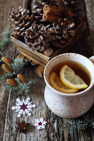 Christmas mood: kopje thee met citroen en dennenappels in een mand en kaneelstokjes