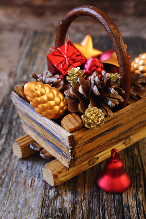 festive pine cones: New Years basket with Christmas-tree decorations and pine cones. Focus selective