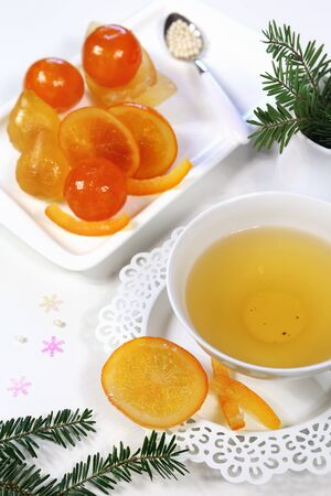 candied fruits: Candied fruits: slices of oranges and cup of green tea and fir branches