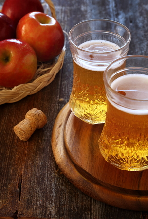 palatable: Two cups of Apple Cider and red apples in wicker basket
