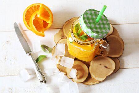 sappy: Cold Orange juice in a glass mug. Focus selective