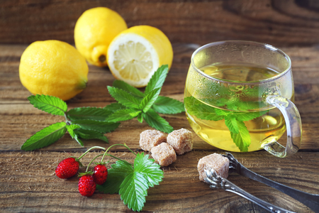 pellucid: Mint tea in a glass cup with lemons and strawberry. Toned image. Focus selective Stock Photo