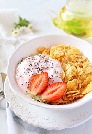 dietetical: Healthy breakfast: corn flakes in bowl, yogurt, strawberries and chia seeds