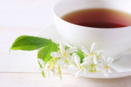 refinement: Jasmine tea in a white bone china cup on white background. Focus selective