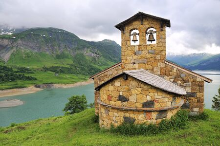 French Alps: Church on the mountain lake shore