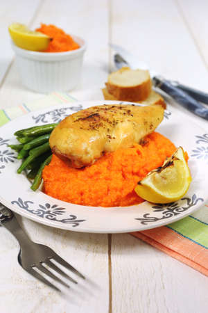 Bright dinner: roast chicken and carrot puree Stock Photo
