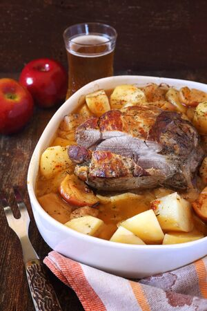 Stewed pork in apple cider with potatoes and apples Stock Photo