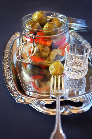 Pickled Brussels sprouts with vegetables and glass of vodka