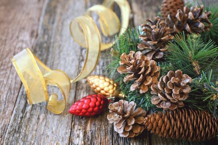 goldish: Pine cones and New-Year tree decorations on a wooden backgroundToned image Stock Photo