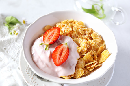 neatness: Healthy breakfast: corn flakes in bowl, yogurt, strawberries and chia seeds