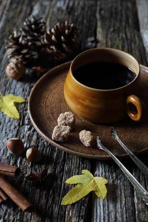 sombre: Autumn mood: cup of coffee, nuts and autumn leaves