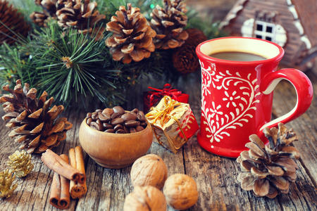 newyear: Cup of coffee, pine cones and New-Year tree decorations on a wooden background. Toned image Stock Photo