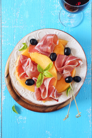 parma ham: Parma ham with melon and glass of red wine Stock Photo