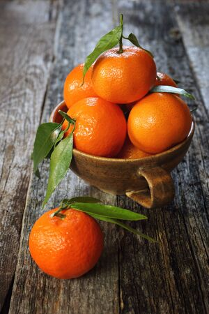 palatable: Tangerines with green leaves on old wooden table