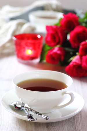 women subtle:  Valentines Day: Romantic Tea Party for two with burning candles and bouquet of red roses