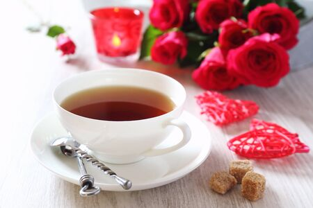 women subtle:  Valentines Day: Romantic Tea drink with burning candle and bouquet of red roses Stock Photo