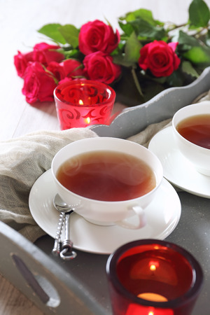 Valentines Day: Romantic Tea Party for two with burning candles and bouquet of red roses