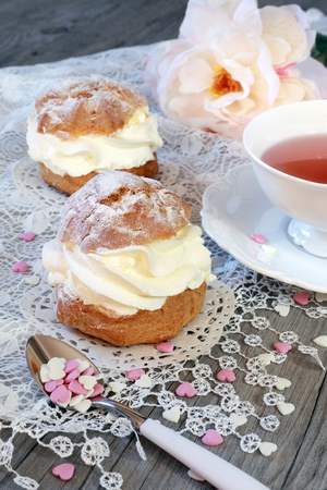 Valentines Day: Romantic tea drinking with pastry chantilly cream and hearts and pink peony