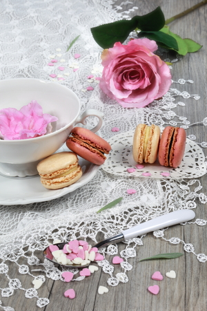 Valentines Day: Romantic tea drinking with macaroon and hearts and and pink flowers