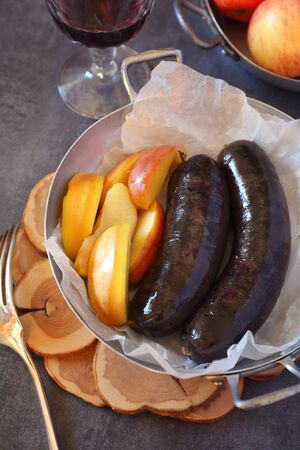 Traditional French cuisine: Blood sausage, apples and glass of red wine Archivio Fotografico