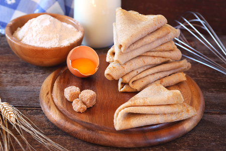 Pancakes and ingredients: flour, milk, sugar on wooden background Stock Photo