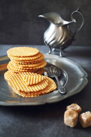 French waffles, traditional norman biscuit and vintage dish, dark photo