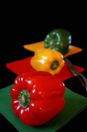 Tri-color bell peppers: red, yellow, green on black background. Focus selective