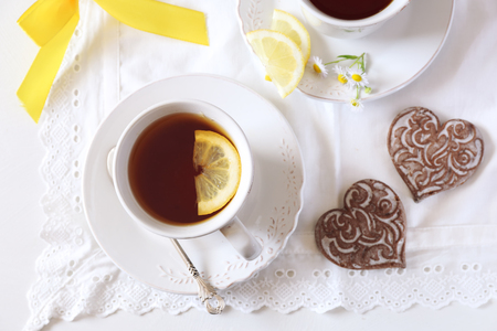 joyous: Two cups of lemon tea and two gingerbread on white table. Top view Stock Photo