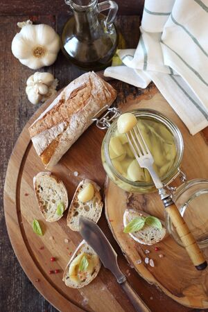 Appetizer: garlic confit in jar and franch spread bread. Top view Stock Photo