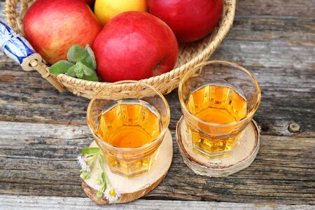 Apple juice in two glass on old wooden table Stock Photo