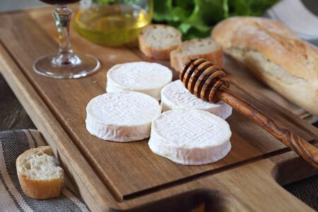 Soft French goat cheese Rocamadour, bread, honey, lettuce and glass of red wine. Focus selective Archivio Fotografico