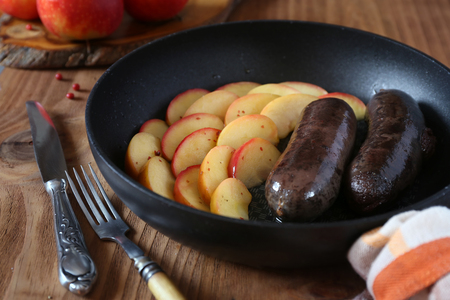Traditional French cuisine: fried blood sausage and apples  Archivio Fotografico