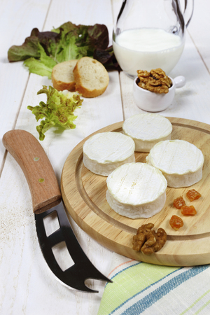 Soft French goat cheese, milk and walnuts on a wooden plate
